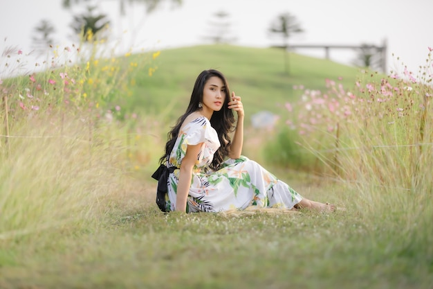 Il sorriso felice delle belle donne asiatiche del ritratto e si rilassa seduto nel giardino fiorito
