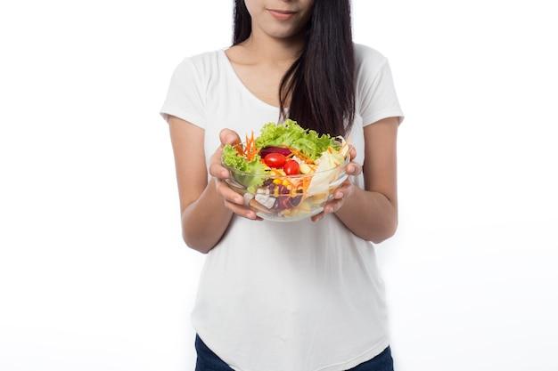 Ritratto di bella giovane donna asiatica che mangia insalata di verdure isolata su bianco.
