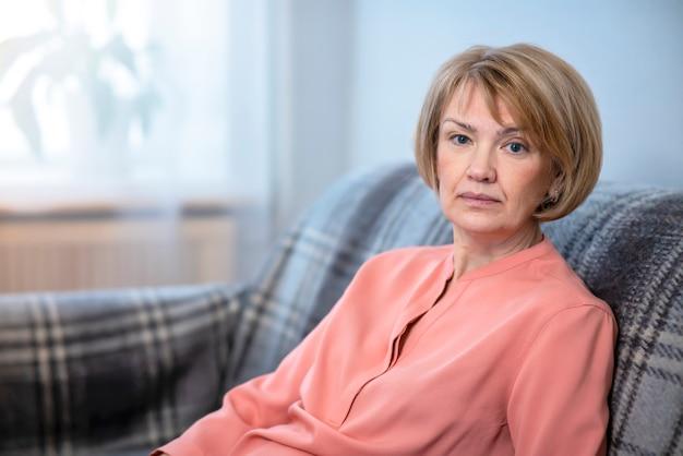 Ritratto di bella donna attraente, signora matura senior anziana adulta che si siede sullo strato a casa dentro