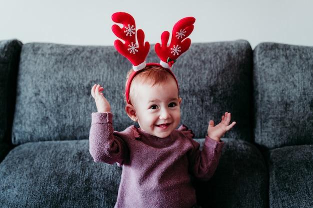 Ritratto di bella bambina a casa indossando un diadema di renne rosse.