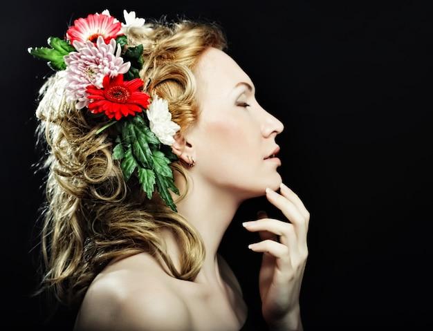 Ritratto di una bella ragazza bionda con fiori tra i capelli