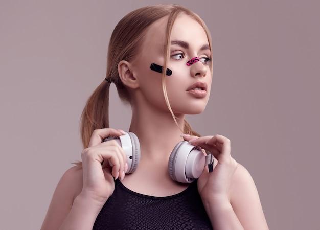 Ritratto di bella ragazza bionda con cerotti glamour sul viso ascoltando musica in cuffie bianche in studio