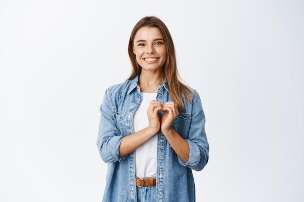 Ritratto di bella ragazza bionda con un sorriso felice, mostrando ti amo gesto del cuore sul petto, mostrando la sua simpatia e sentimento romantico, muro bianco