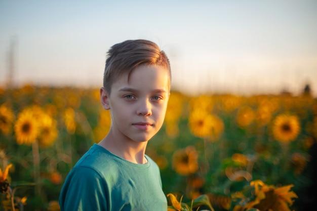 Ritratto di bello ragazzo biondo del bambino sul campo di girasole di estate