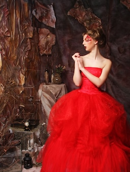 Ritratto di una bella donna bionda in abito rosso. trucco e acconciatura creativi. girato in una casa di fantasia.