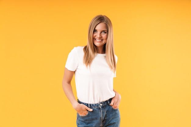 Ritratto di bella donna bionda che indossa una maglietta casual che sorride davanti mentre in piedi con le braccia in tasca isolate sul muro giallo in studio