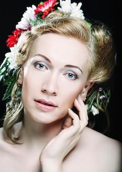 Ritratto di bella donna bionda con fiori tra i capelli