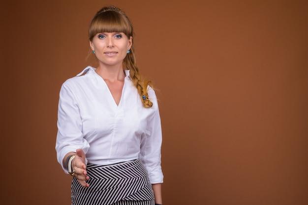 Ritratto di bella donna di affari bionda con capelli intrecciati che dà la stretta di mano