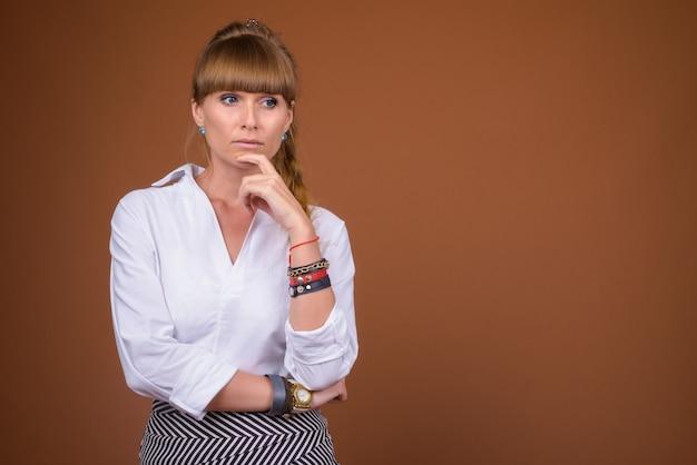 Ritratto di bella bionda imprenditrice con capelli intrecciati pensando