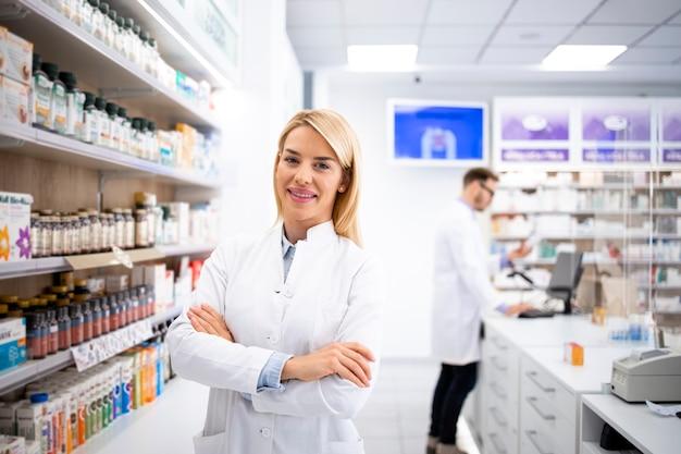 Ritratto di farmacista femmina bionda bella in piedi nel negozio di farmacia dallo scaffale con farmaci.