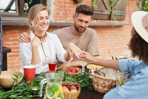 Ritratto di bella donna bionda che mostra l'anello di fidanzamento agli amici durante la cena all'aperto