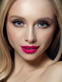 Ritratto di bella donna bionda con trucco luminoso. occhi smokey dorati e labbra rosa. cura della pelle di lusso e moderno concetto di trucco di moda.