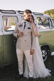 Il ritratto di bella sposa abbraccia il suo sposo bello vicino alla retro-automobile