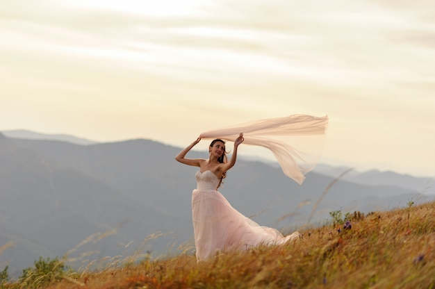 Ritratto di una bella sposa su un paesaggio di montagne autunnali. la ragazza tiene tra le mani un velo sopra la testa. un forte vento soffia i suoi capelli, il vestito e il velo.