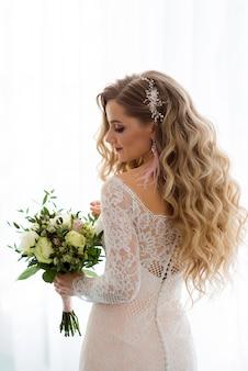 Ritratto di una bella sposa con un bouquet su uno sfondo chiaro