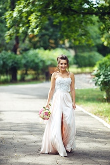 Ritratto di bella sposa con un bouquet da sposa per una passeggiata nel parco. la donna felice della persona appena sposata sta fra i cespugli verdi nel giardino. sposa sorridente. giorno del matrimonio. moda sposa.