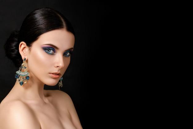Ritratto di bella donna brunet con orecchini blu in posa. trucco alla moda moderna.