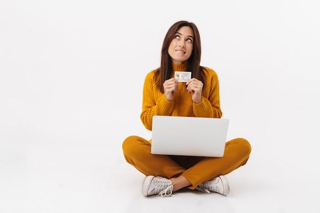 Ritratto di una bella donna bruna adulta che tiene in mano un computer portatile e una carta di credito mentre è seduto con le gambe incrociate isolato su bianco