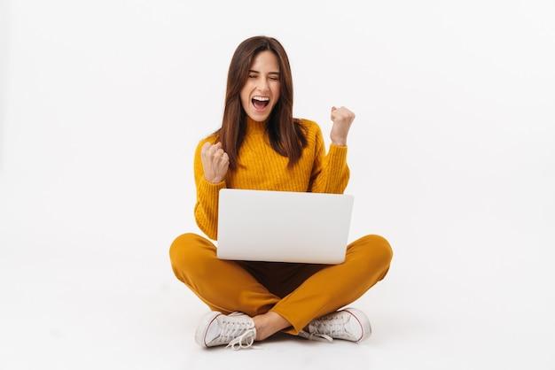 Ritratto di bella donna bruna adulta che si rallegra e tiene in mano un computer portatile mentre è seduto con le gambe incrociate isolato su bianco