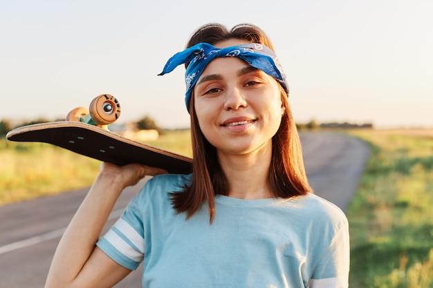 Ritratto di bella donna bruna che indossa maglietta blu e fascia per capelli, tenendo lo skateboard sulla spalla e guardando la telecamera, godendosi lo skateboard in estate, passatempo attivo.