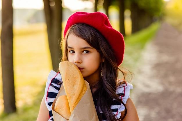 Ritratto bella ragazza castana che tiene una baguette francese