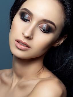 Ritratto di bella donna castana con trucco da sera. occhi smokey multicolore lucidi. cura della pelle di lusso e moderno concetto di trucco di moda.