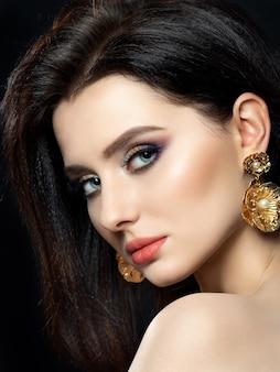 Ritratto di bella donna castana con orecchini d'oro. occhi smokey multicolore lucidi. cura della pelle di lusso e moderno concetto di trucco di moda.