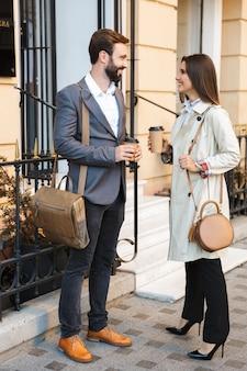 Ritratto di bella coppia d'affari uomo e donna in abbigliamento formale che bevono caffè da asporto e parlano insieme mentre si incontrano sulla strada della città city