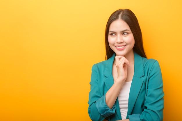 Ritratto di bella donna d'affari in abito verde su sfondo giallo