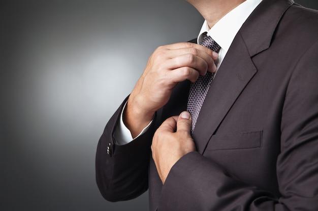 Il ritratto del bello uomo d'affari in costume nero lega la propria cravatta