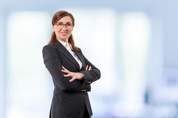 Il ritratto di bella donna di affari 50 orecchie vecchie in armi attraversate posa nell'ufficio.