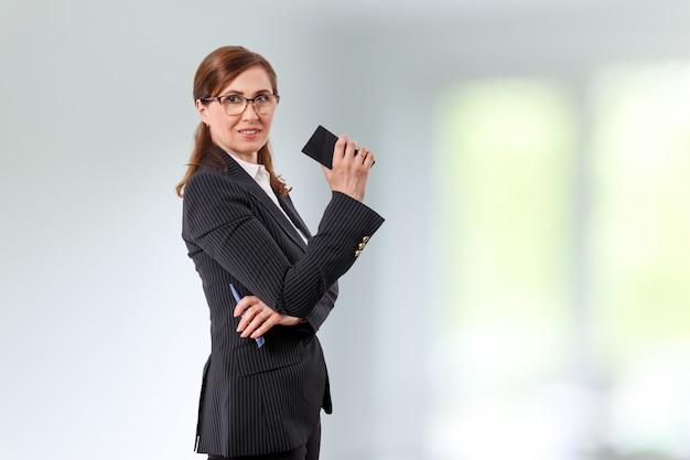 Ritratto di una bella imprenditrice 50 orecchie vecchie con il cellulare in ufficio.