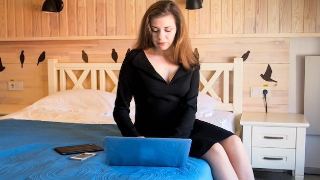 Ritratto di bella donna d'affari seduta sul letto in una camera d'albergo e utilizzando il computer portatile