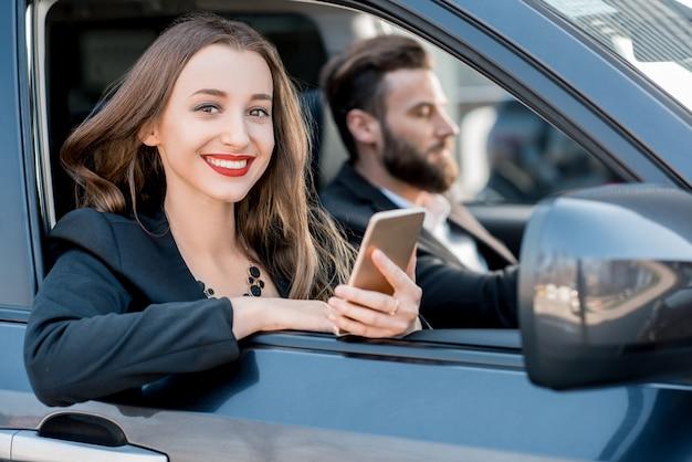 Ritratto di una bella donna d'affari seduta in macchina con autista uomo d'affari