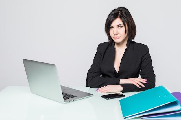 Ritratto di una bella donna d'affari seduta alla scrivania che lavora isolata su bianco