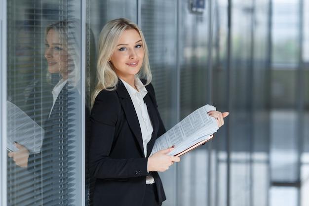 Ritratto di bella donna d'affari sorridente e in piedi con la cartella in ufficio.
