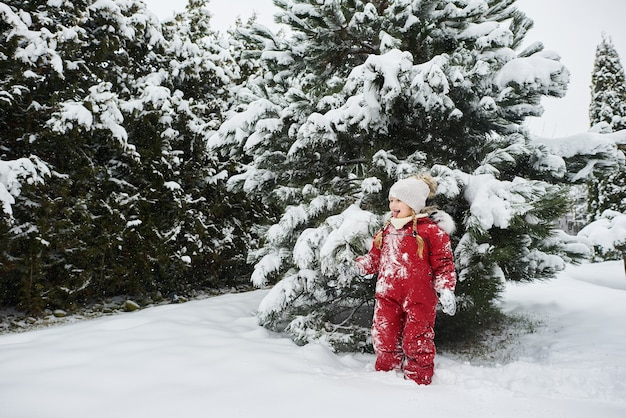 Ritratto di un bel bambino caucasico in una tuta rossa