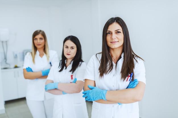 Ritratto di bello assistente di laboratorio femminile caucasico in uniforme bianca