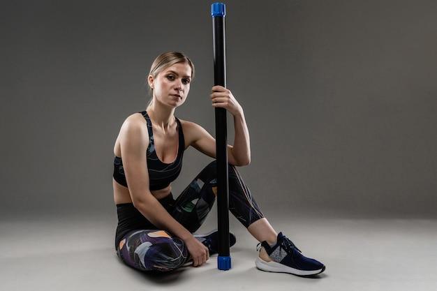 Ritratto di bella donna caucasica con capelli lunghi biondi in abbigliamento sportivo fare esercizi con inventario sportivo