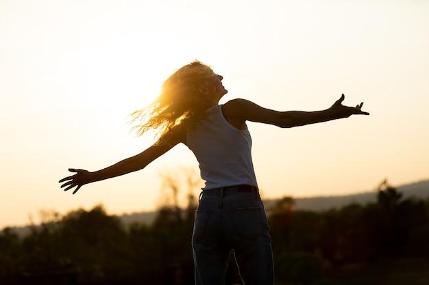 Ritratto di bella donna caucasica che sorride e che distoglie lo sguardo al parco. felice giovane donna al tramonto in natura con le mani aperte