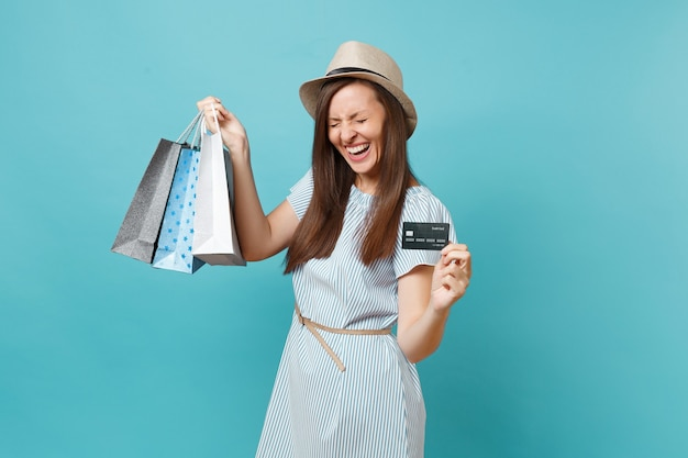 Ritratto di bella donna caucasica in abito estivo, cappello di paglia che tiene pacchetti borse con acquisti dopo lo shopping, carta di credito bancaria isolata su sfondo blu pastello. copia spazio per la pubblicità.