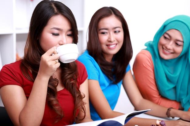 Ritratto di bella studentessa universitaria che beve una tazza di tè e legge un libro mentre i suoi due amici la guardano