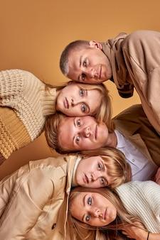 Ritratto di bei giovani caucasici fiduciosi isolati su sfondo marrone