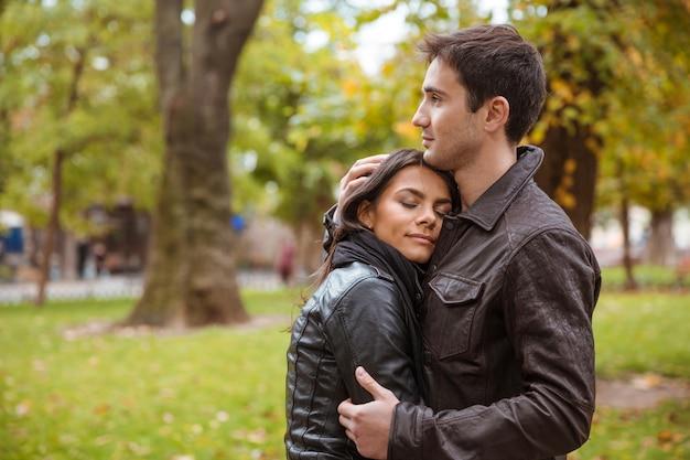 Ritratto di una bella coppia che abbraccia all'aperto nel parco