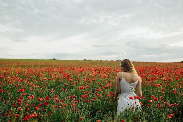 Ritratto di una bella ragazza bionda carina nel campo di papaveri in estate in un abito bianco