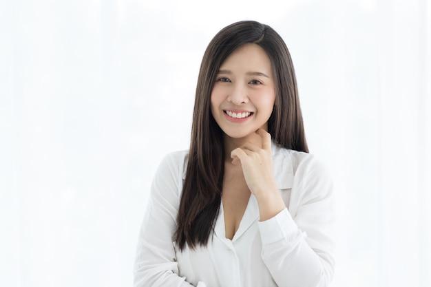 Ritratto di bella e carina donna asiatica con i capelli lunghi in piedi con un sorriso amichevole sul viso e alzare una mano toccandole il mento in modo pensante.