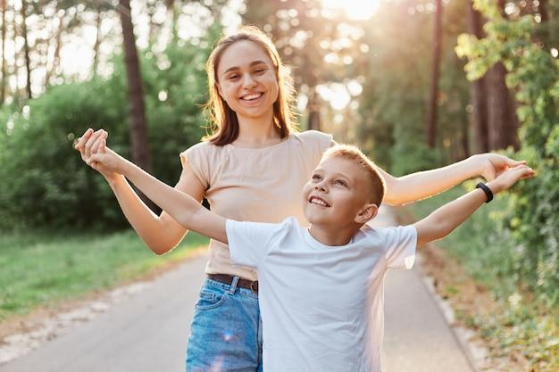Ritratto di bella donna dai capelli scuri in maglietta beige che gioca con suo figlio nel parco estivo, donna che tiene le mani del ragazzo, guardando la macchina fotografica, famiglia che esprime felicità.