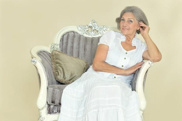 Ritratto di bella donna anziana su sedia vintage in camera