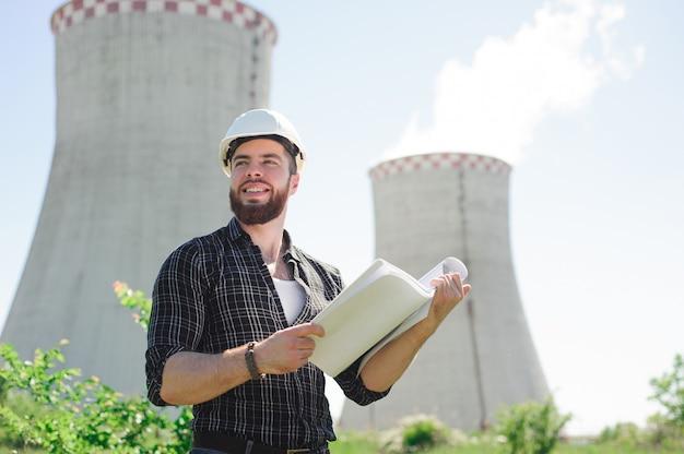Ritratto di un bellissimo ingegnere al lavoro con il telefono.