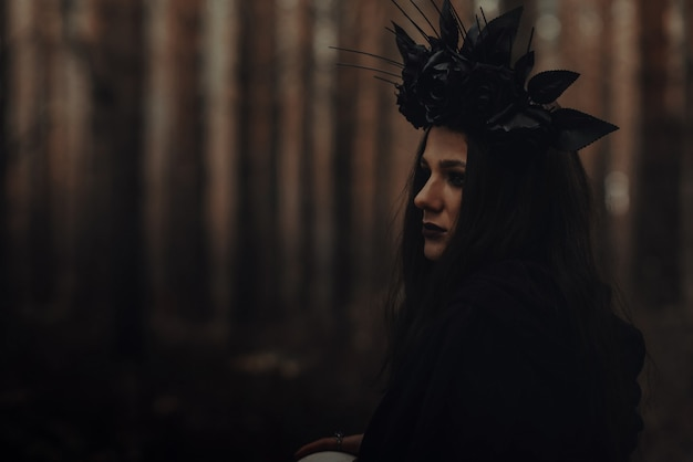 Ritratto di una bella strega strega cattiva in una foresta oscura